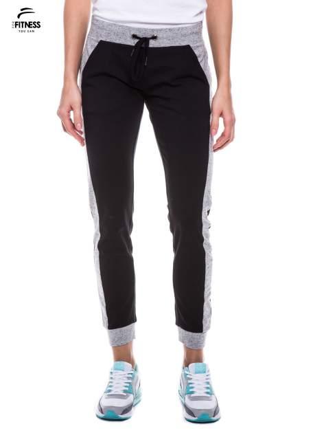 Czarne spodnie dresowe damskie z kontrastowymi lampasami po bokach