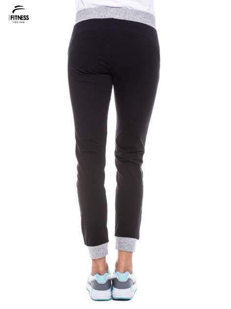 Czarne spodnie dresowe damskie z kontrastowymi lampasami po bokach                                  zdj.                                  4