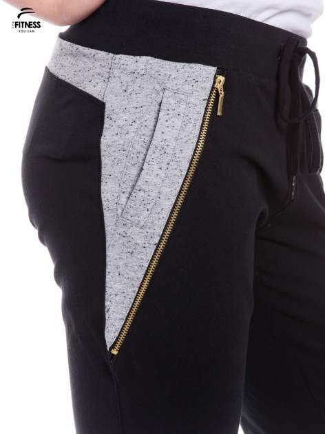 Czarne spodnie dresowe damskie z suwakiem i kontrastowymi wstawkami po bokach                                  zdj.                                  5