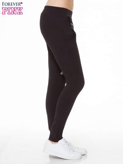 Czarne spodnie dresowe typu baggy z naszywkami                                  zdj.                                  3