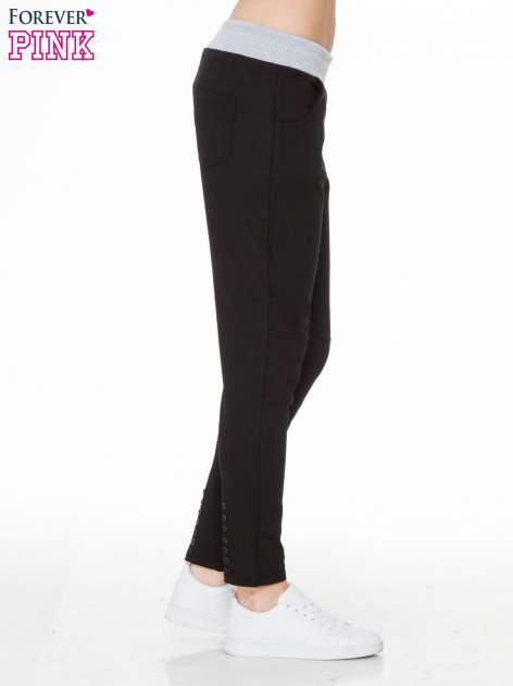 Czarne spodnie dresowe z guziczkami na nogawkach                                  zdj.                                  3