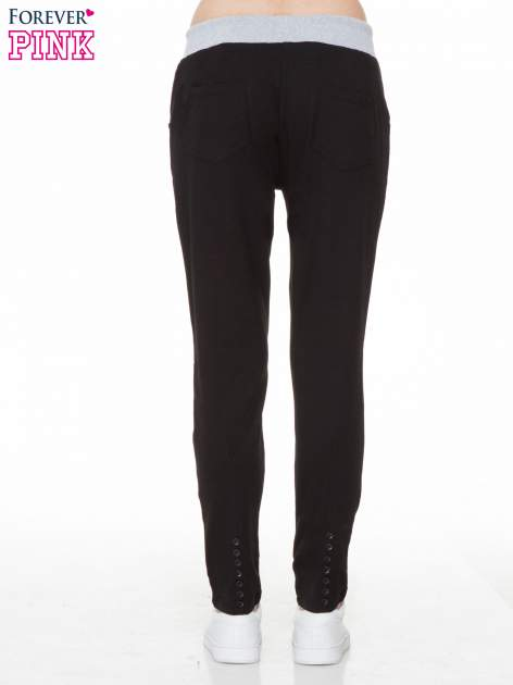 Czarne spodnie dresowe z guziczkami na nogawkach                                  zdj.                                  4