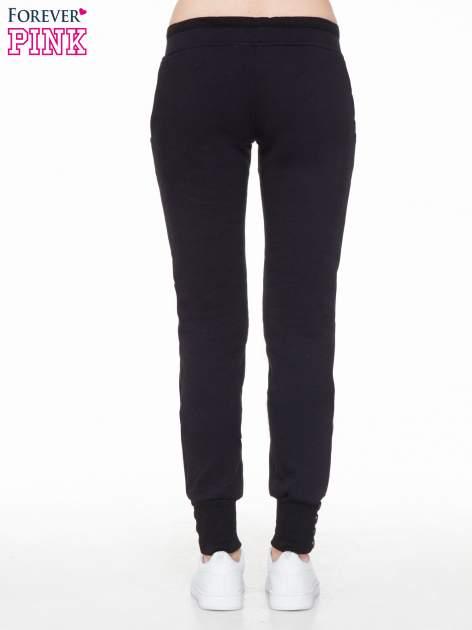 Czarne spodnie dresowe z guziczkami przy ściągaczu                                  zdj.                                  4