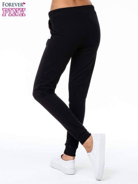Czarne spodnie dresowe z kolorową wstawką                                  zdj.                                  2