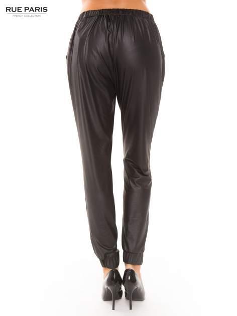Czarne spodnie dresowe ze zwężanymi nogawkami z efektem połysku                                  zdj.                                  4