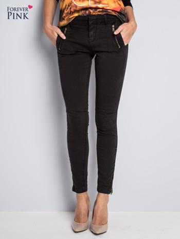 Czarne spodnie typu rurki z suwakami wzdłuż nogawek i z przodu