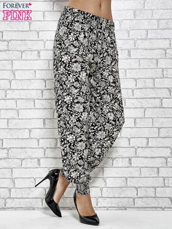 Czarne zwiewne spodnie alladynki we wzór kwiatków                                  zdj.                                  1