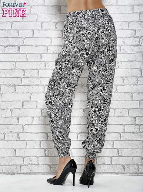 Czarne zwiewne spodnie alladynki we wzór roślinny                                  zdj.                                  2