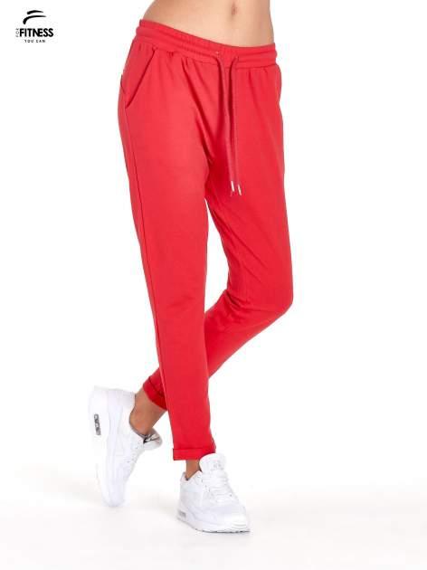 Czerwone spodnie dresowe z powijaną nogawką