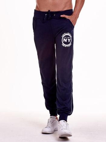 Granatowe dresowe spodnie męskie z lampasami po bokach i aplikacją                                  zdj.                                  1