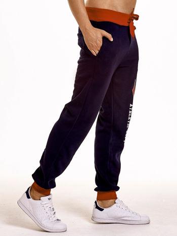 Granatowe dresowe spodnie męskie z napisem CALIFORNIA i naszywką                                  zdj.                                  3