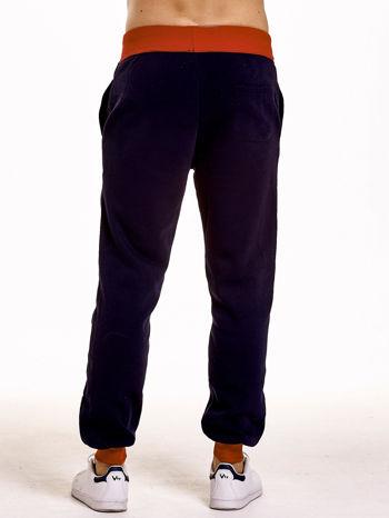 Granatowe dresowe spodnie męskie z napisem CALIFORNIA i naszywką                                  zdj.                                  2