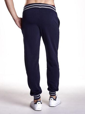 Granatowe dresowe spodnie męskie z naszywkami i kieszeniami                                  zdj.                                  3