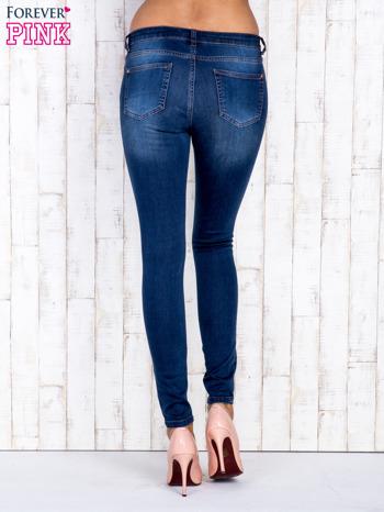 Granatowe jeansowe spodnie rurki z przetarciami                                  zdj.                                  3