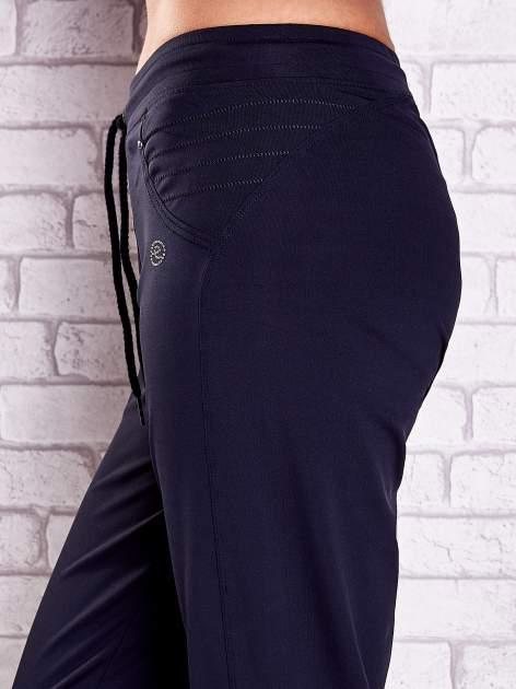 Granatowe spodnie capri z haftowanymi wstawkami PLUS SIZE                                  zdj.                                  5