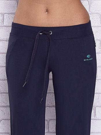 Granatowe spodnie capri z motywem pasków na nogawkach                                  zdj.                                  4