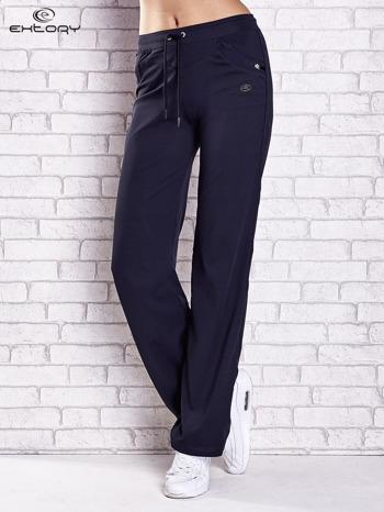Granatowe spodnie dresowe z aplikacjami z błyszczących dżetów                                  zdj.                                  1
