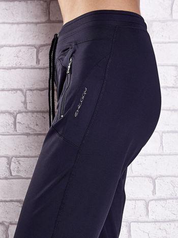 Granatowe spodnie dresowe z kieszeniami i przeszyciami                                  zdj.                                  5