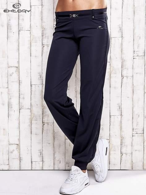 Granatowe spodnie dresowe z ozdobnym paskiem                                  zdj.                                  1