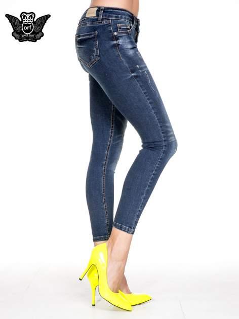 Granatowe spodnie skinny jeans z przecieraną nogawką z przodu                                  zdj.                                  3