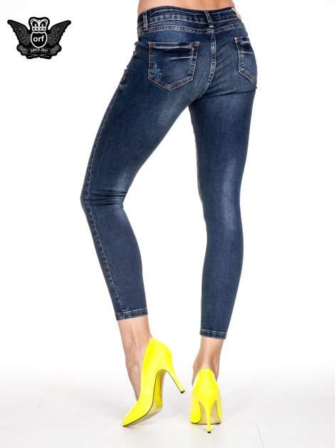 Granatowe spodnie skinny jeans z przecieraną nogawką z przodu                              zdj.                              4