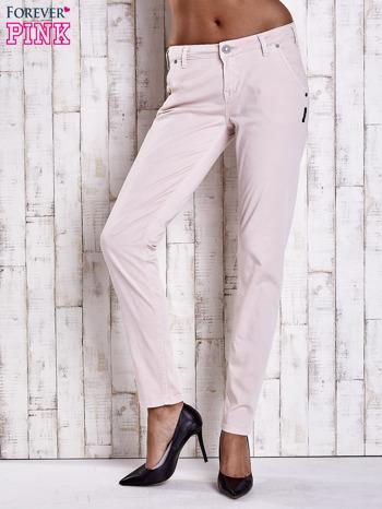 Jasnobeżowe materiałowe spodnie z przeszyciami na kieszeniach
