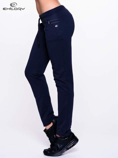 Jasnogranatowe spodnie dresowe z dżetami przy kieszeniach                                  zdj.                                  3
