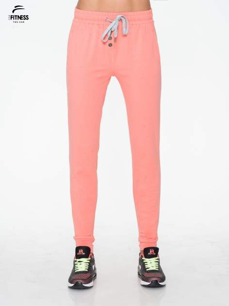 Jasnokoralowe spodnie dresowe typu baggy z guzikami                                  zdj.                                  1