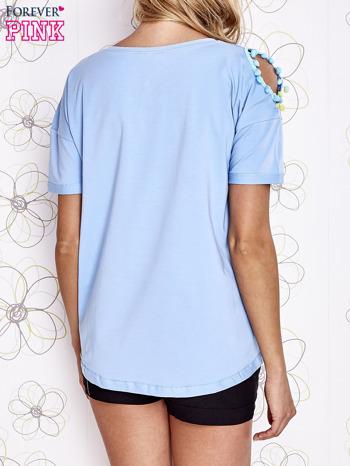 Jasnoniebieski t-shirt z naszywką motyla i pomponami                                  zdj.                                  2
