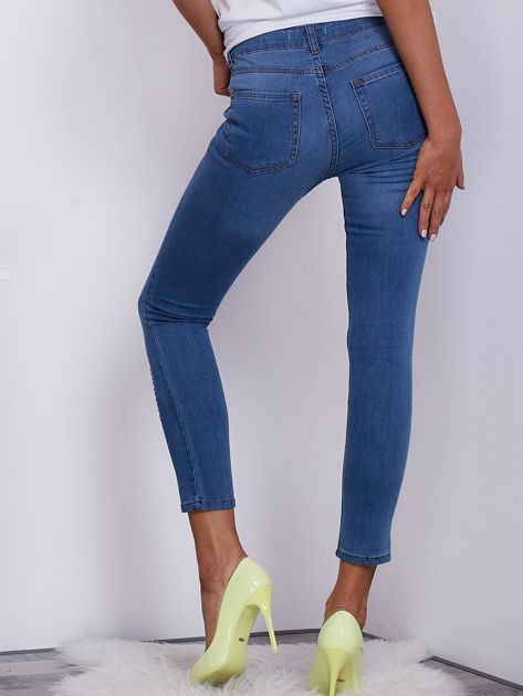 Jasnoniebieskie jeansy damskie o kroju slim z drobnymi przetarciami                              zdj.                              2