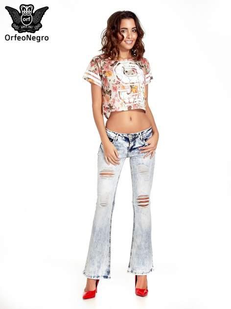 Jasnoniebieskie spodnie jeansowe dzwony z dziurą na kolanie                                  zdj.                                  4