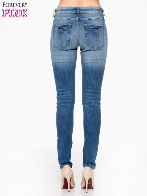 Jasnoniebieskie spodnie jeansowe rurki z przeszyciami na kieszeniach                                  zdj.                                  4