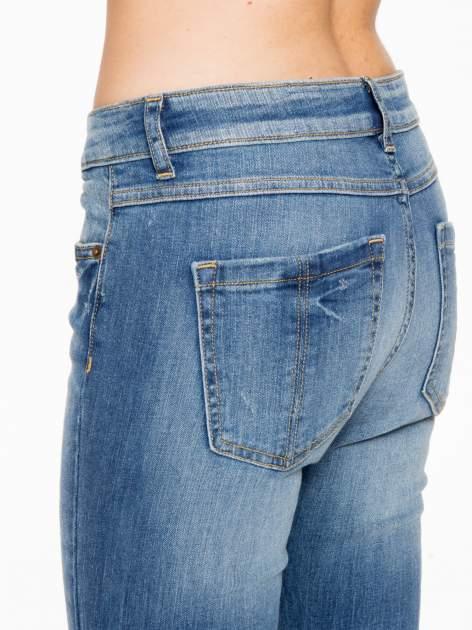 Jasnoniebieskie spodnie jeansowe rurki z przeszyciami na kieszeniach                                  zdj.                                  9