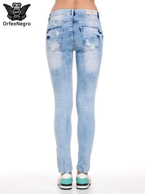 Jasnoniebieskie spodnie jeansowe rurki z rozdarciami i przetarciami                                  zdj.                                  4