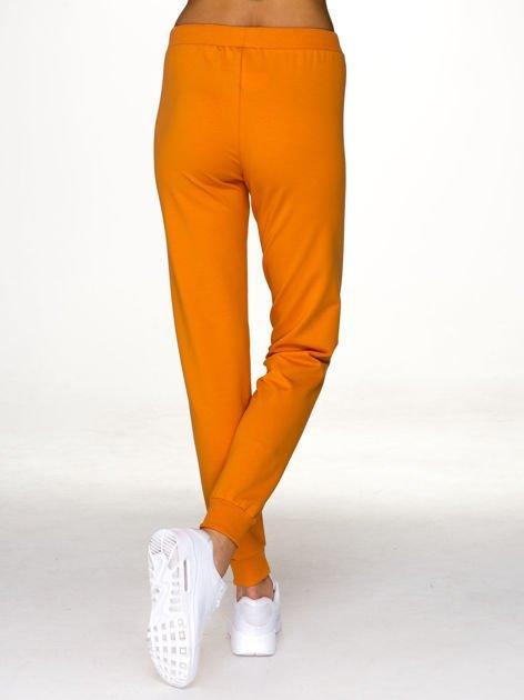 Jasnopomarańczowe spodnie dresowe z napisem BROOKLYN