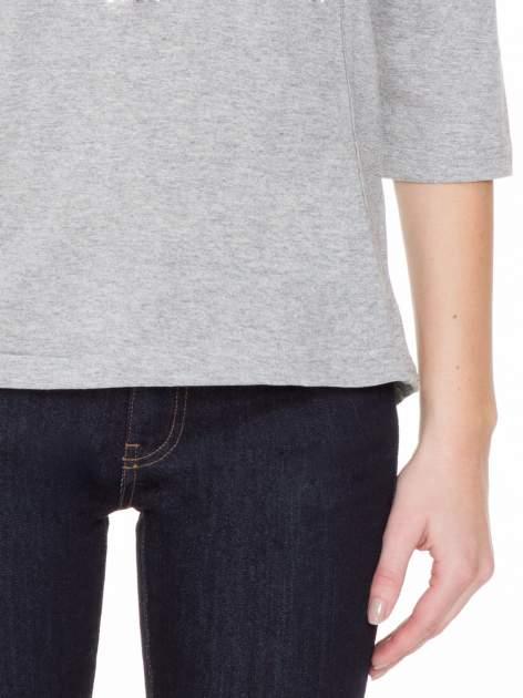 Jasnoszara melanżowa gładka bluzka z ozdobnymi przeszyciami                                  zdj.                                  5