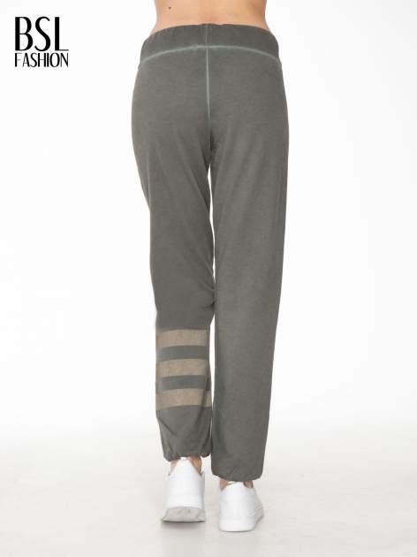 Khaki dresowe spodnie damskie z numerkiem i paskami na nogawkach                                  zdj.                                  4