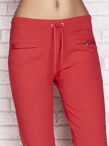Koralowe spodnie dresowe capri z wszytymi kieszonkami                                  zdj.                                  4