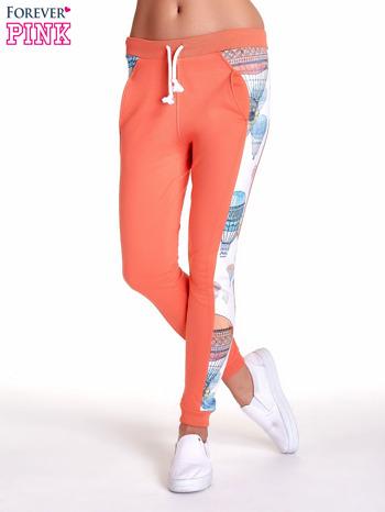 Koralowe spodnie dresowe z lampasem w balony