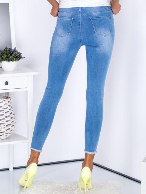 Niebieskie jeansowe rurki z rozdarciami na nogawkach                              zdj.                              2