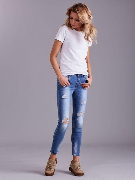 Niebieskie jeansy damskie z przetarciami                              zdj.                              1