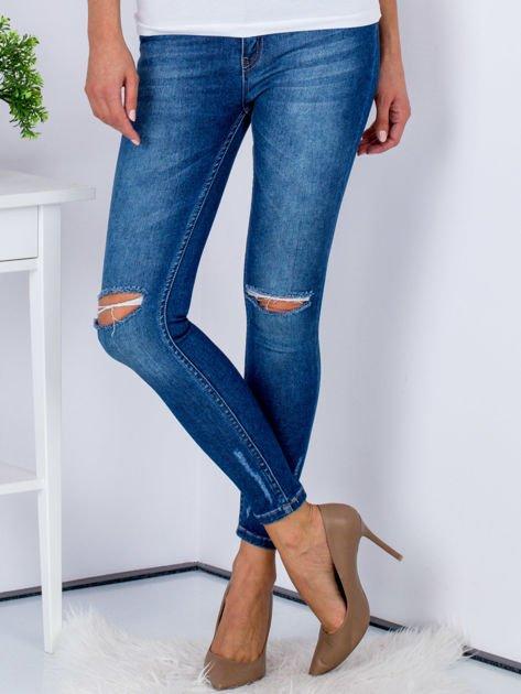 Niebieskie jeansy z rozcięciami na kolanach                              zdj.                              1