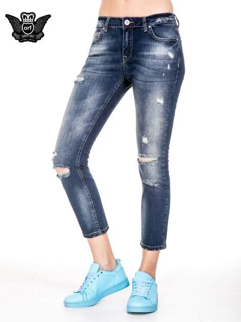 Niebieskie spodnie girlfriend jeans z rozjaśnianą nogawką i dziurami                                  zdj.                                  1