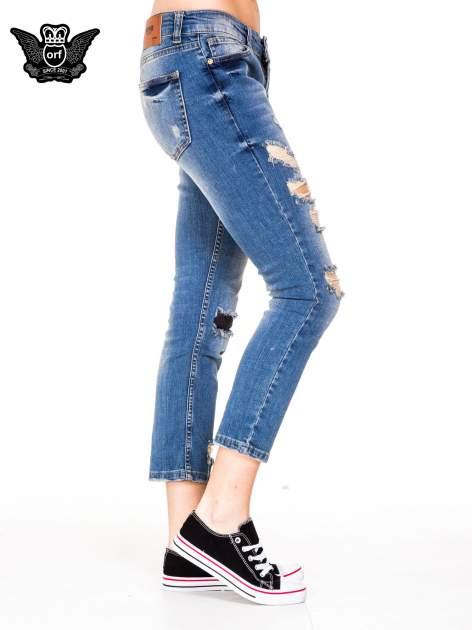 Niebieskie spodnie jeansowe rurki 7/8 z łatą i dziurami                                  zdj.                                  3