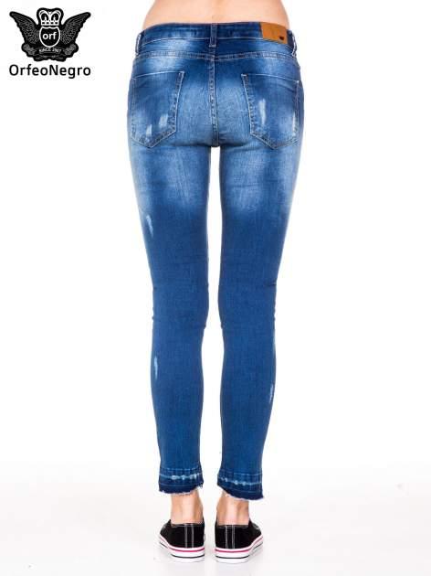 Niebieskie spodnie jeansowe rurki z dziurami i strzępioną nogawką                                  zdj.                                  4
