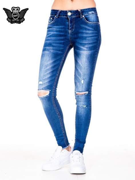 Niebieskie spodnie jeansowe rurki z rozjaśnianą nogawką i rozdarciami na kolanach                                  zdj.                                  1