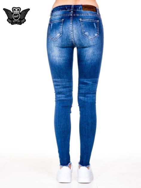 Niebieskie spodnie jeansowe rurki z rozjaśnianą nogawką i rozdarciami na kolanach                                  zdj.                                  5