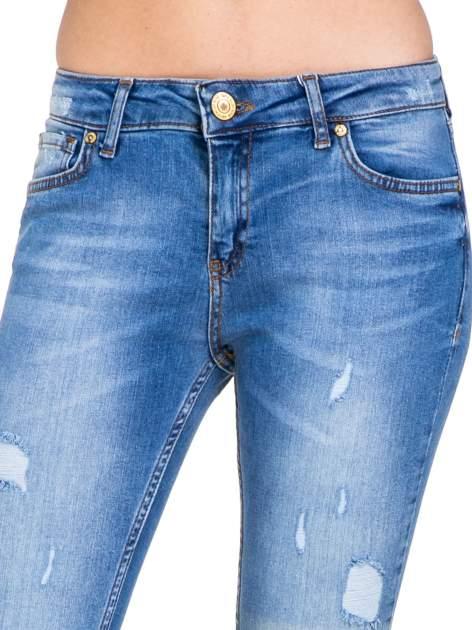 Niebieskie spodnie jeansowe z cieniowaną nogawką z przetarciami                              zdj.                              7