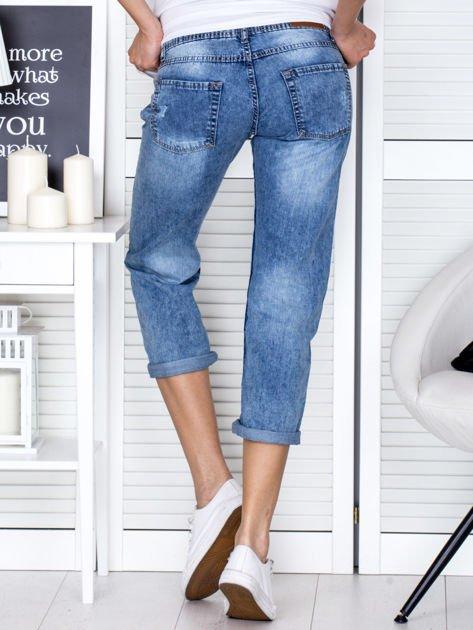 Niebieskie spodnie jeansowe z dekatyzacją i przedarciami                                  zdj.                                  2