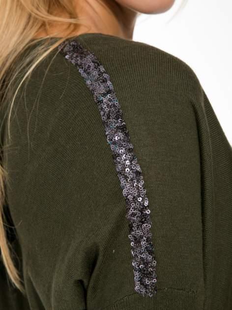 Oliwkowy sweter o nietoperzowym kroju z cekinową aplikacją na rękawach                                  zdj.                                  7